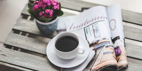 Cup of coffee, magazine and pink potted plant on a table.