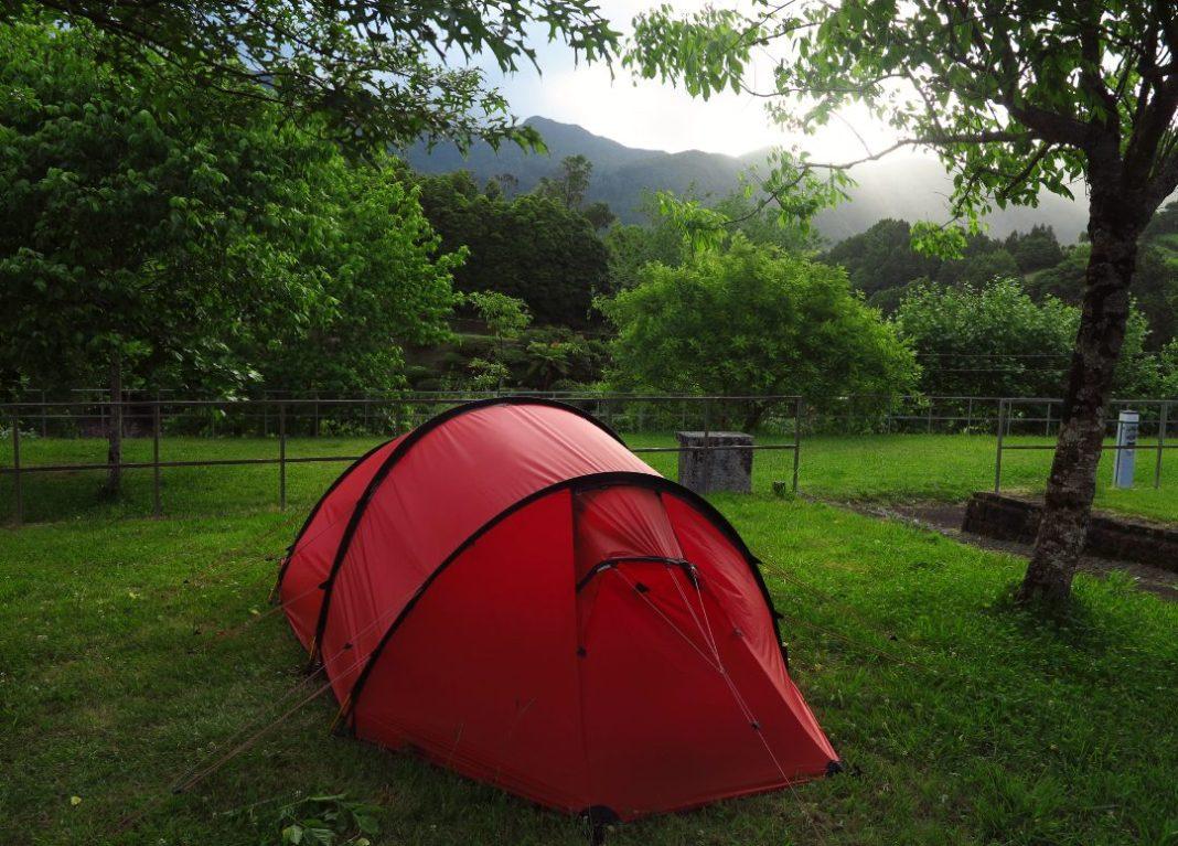 Rotes Zelt auf grüner Wiese