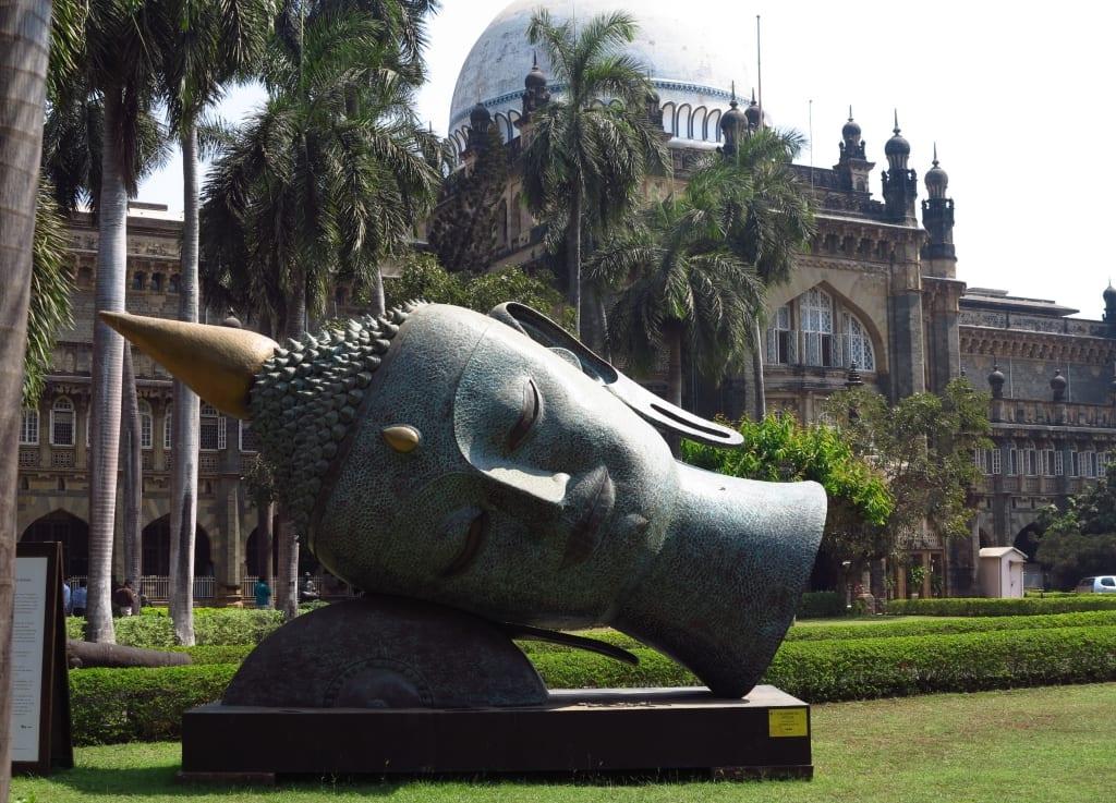 Liegender Buddhakopf vor einem prächtigen Gebäude
