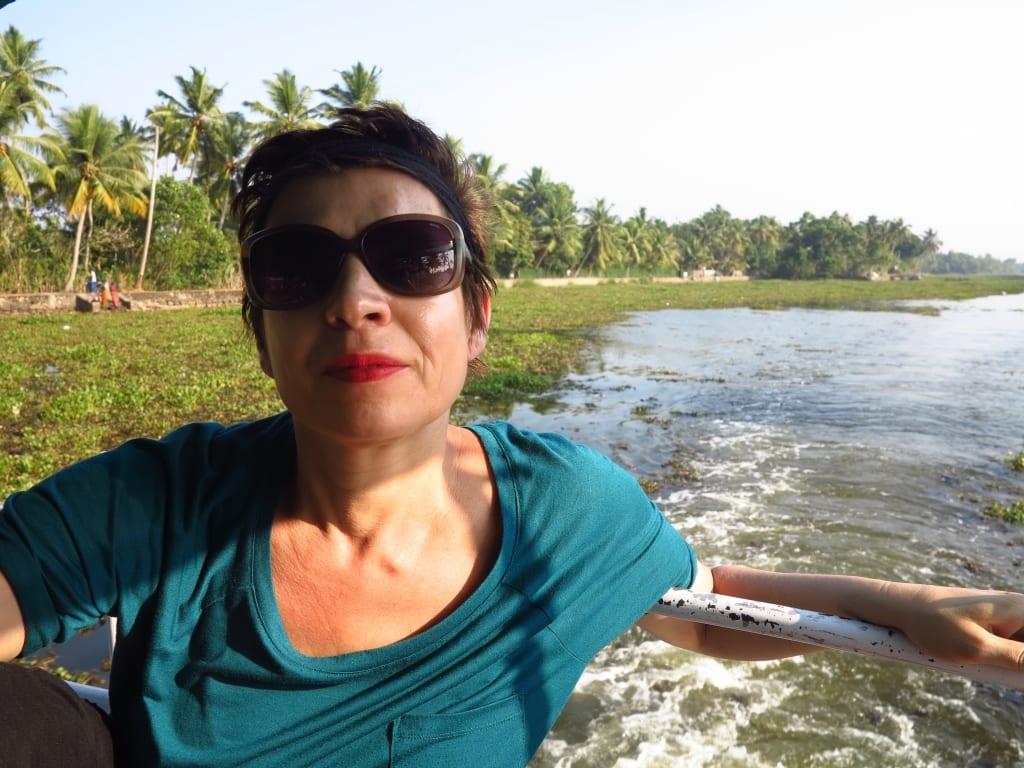 Frau auf Boot, im Hintergrund Palmen