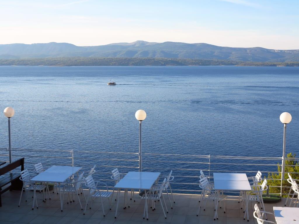 Restaurantterrasse am Meer, dahinter Insel