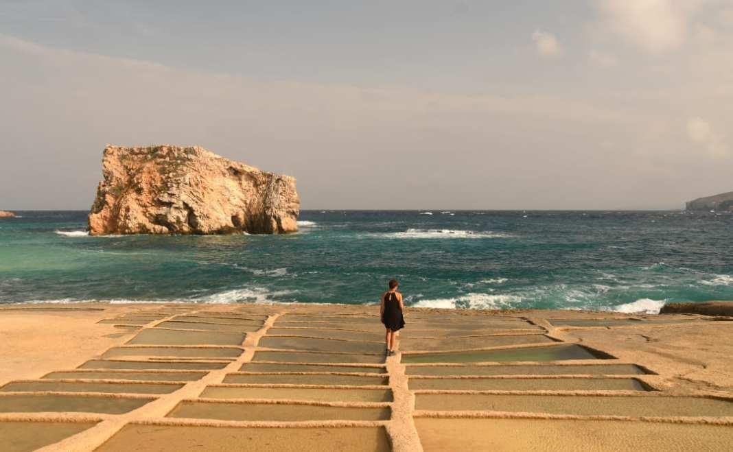 Frau steht auf Salinen am Meer