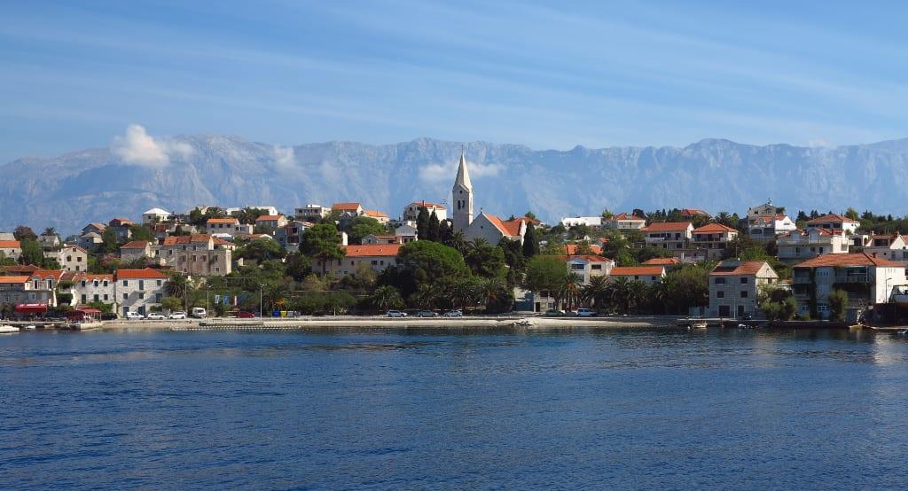 Dorf mit Kirche am Meer, dahinter Berge