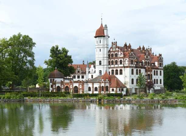 Märchenschloss mit Zinnen spiegelt sich im Wasser