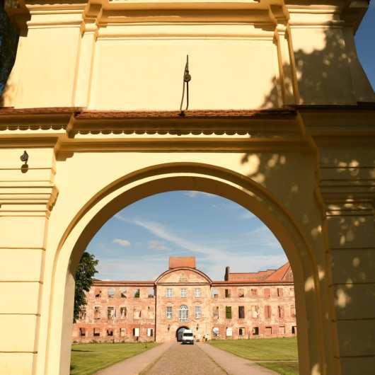 Blick durch ein Tor auf eine Schlossruine