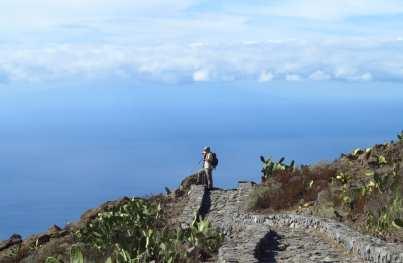Mann steht auf Aussichtspunkt und blickt aufs Meer