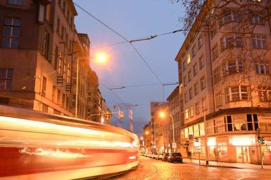 Straßenbahn fährt im Abendlicht durch Straße
