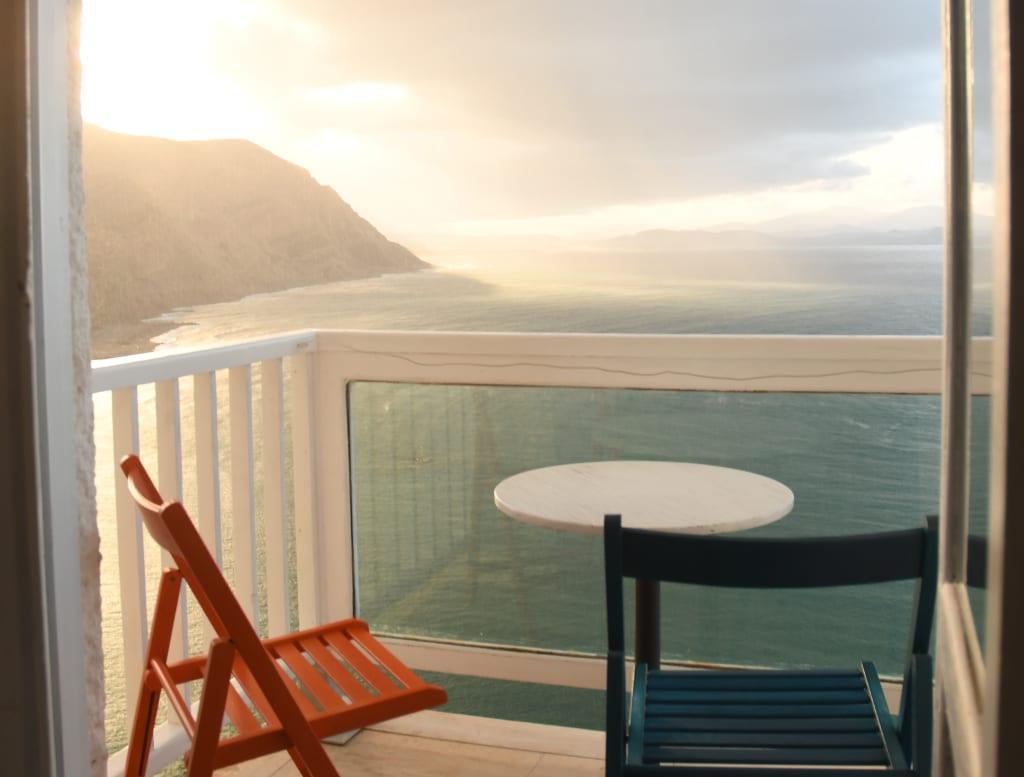 Zwei Stühle auf einem Hotelbalkon auf Kreta, dahinter das Meer