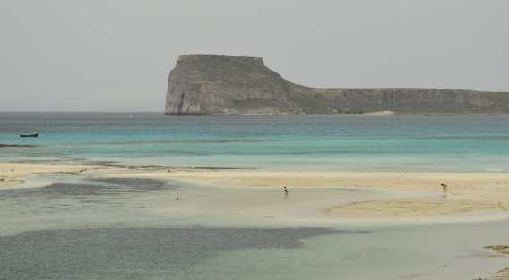 Mensch spaziert auf einem sonst leeren Traumstrand auf Kreta