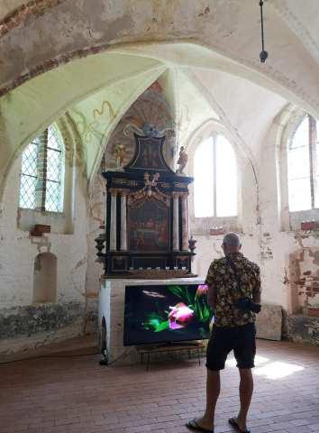 Mann steht in einer Kirche, in der gerade eine Videoinstallation läuft