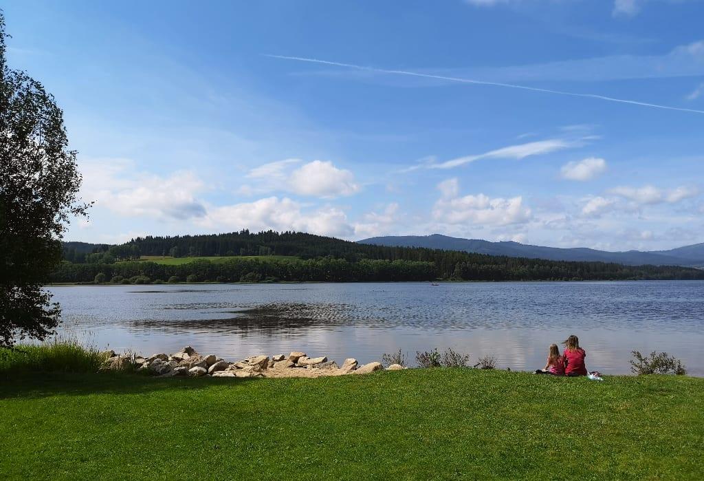 Zwei Leute sitzen an einem Seeufer