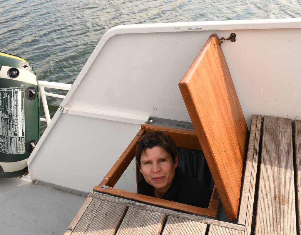 Frau schaut aus einer Luke auf einem Boot