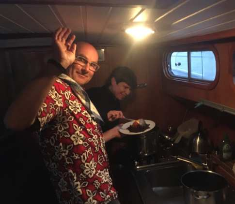 Zwei Personen kochen in einer Schiffskombüse