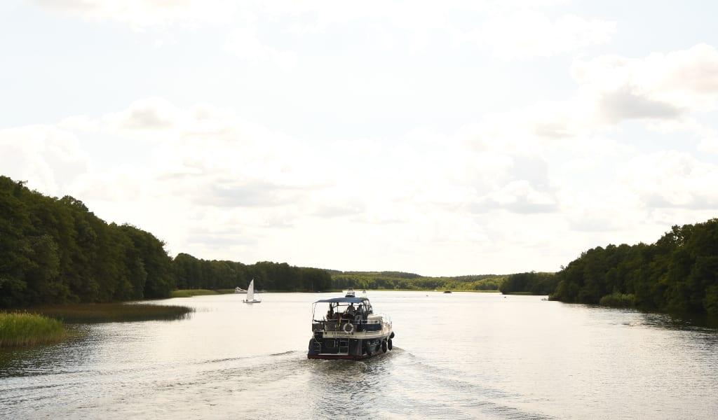 Boot auf See, rechts und links Wald