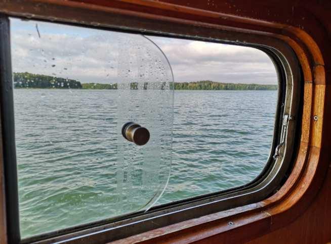 Fenster eines Schiffs mit Seeblick