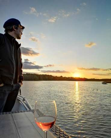Mann blickt auf Sonnenuntergang über einem See