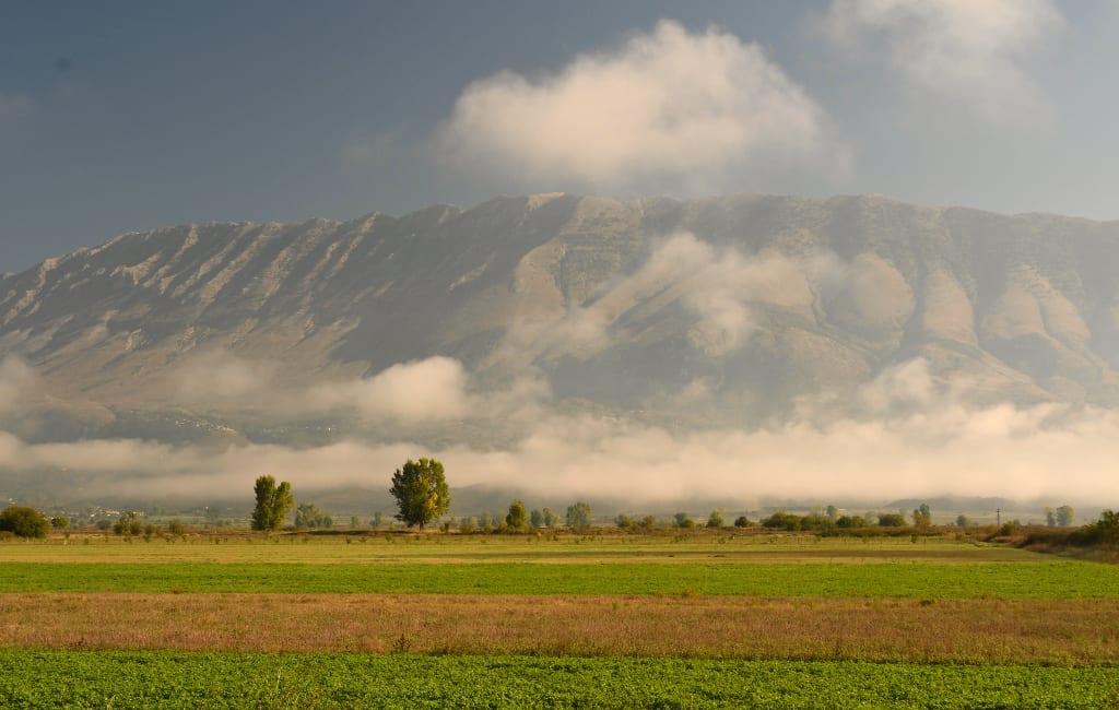 Landschaft mit Bergen, Feldern und Nebel