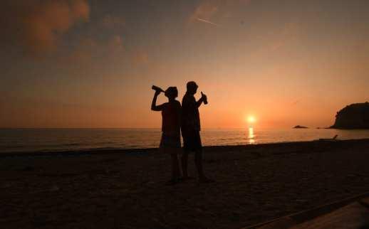 Zwei personen trinken Bier bei Sonnenuntergang am Meer