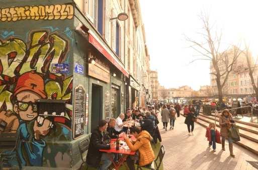 Leute sitzen vor Cafés