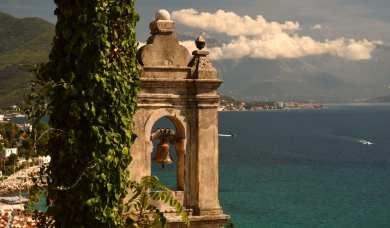 Glockenturm einer Kirche mit dem Meer im Hintergrund