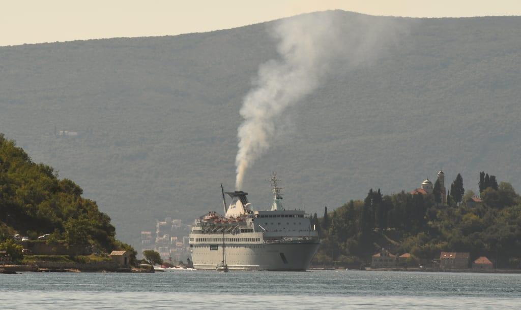 Rauchendes Kreuzfahrtschiff in einer Meeresbucht