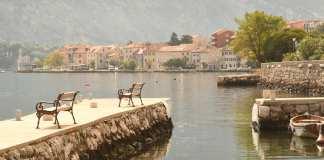Bänke auf einer Mole vor einer Stadt am Meer