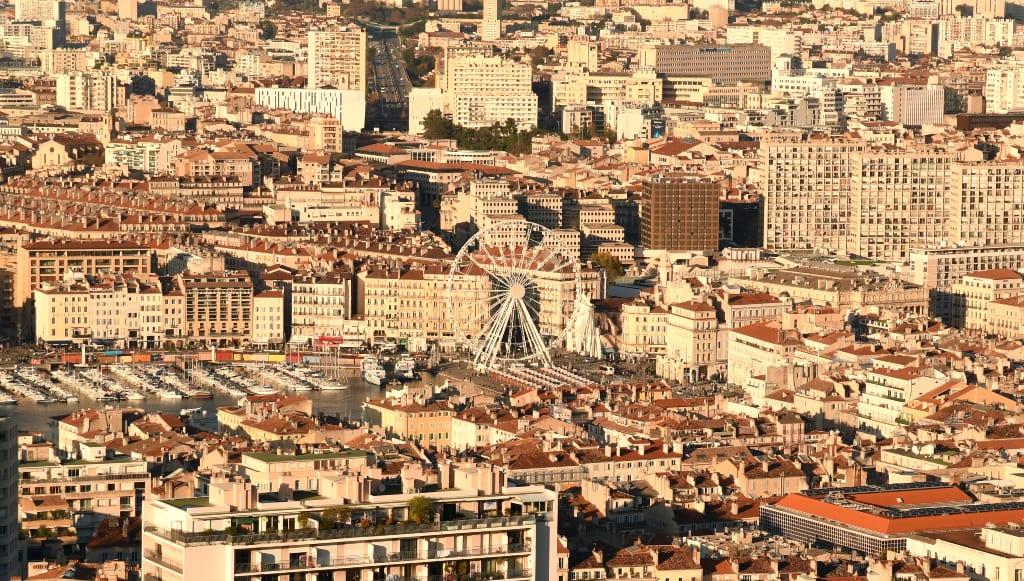 Blick auf eine Stadt mit Riesenrad und Hafen