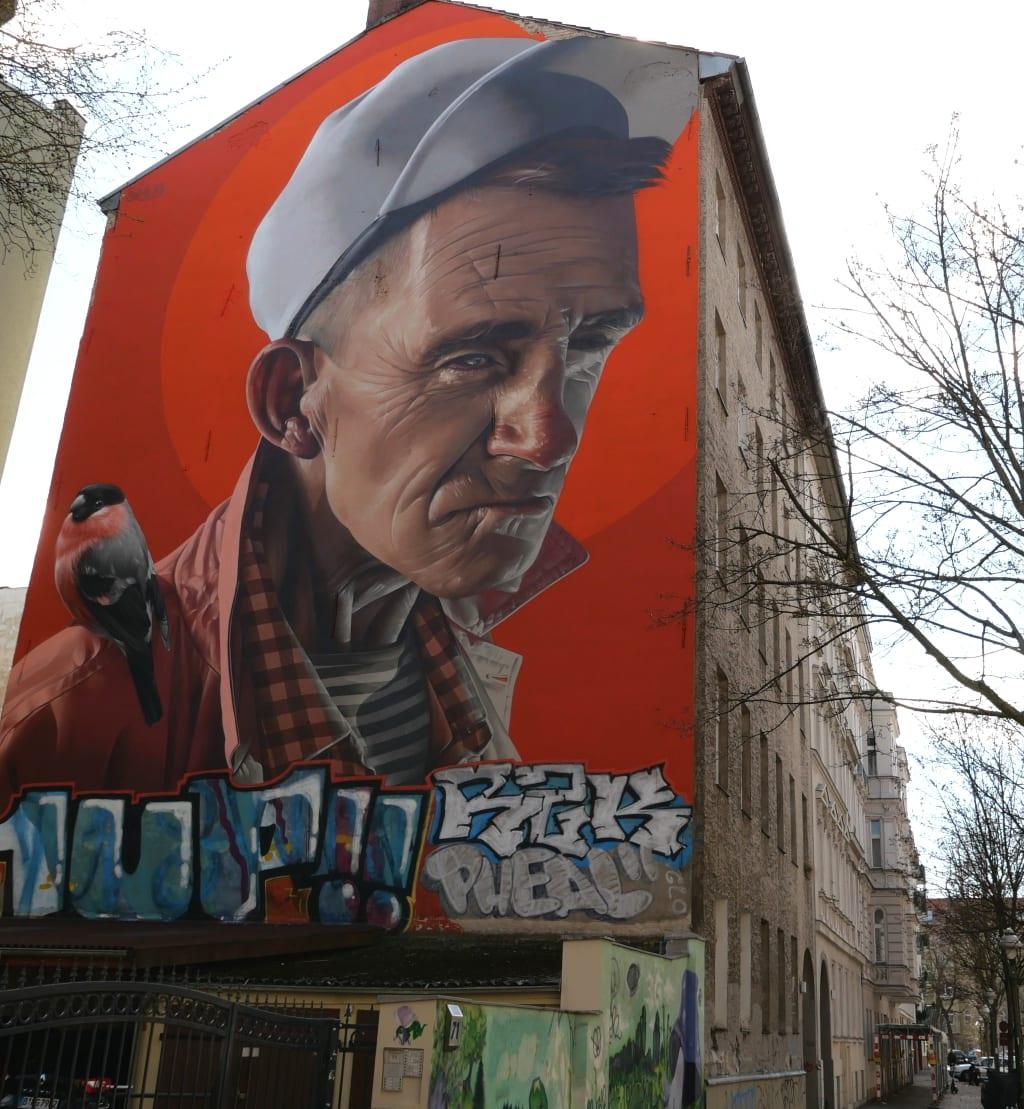 Realistisches Wandgemälde eines Mannes mit Basecap