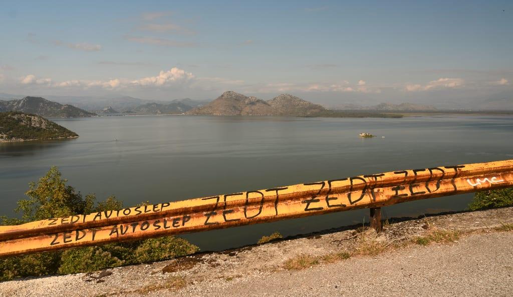 Gelbe Leitplanke entlang eines See