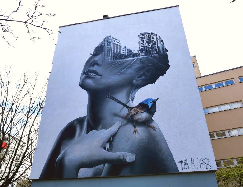 Riesiges Mural einer Frau mit Vogel auf der Schulter