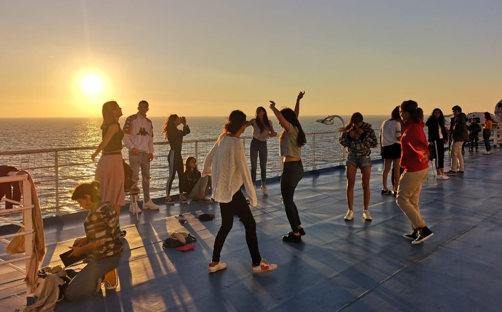 Junge Leute tanzen bei Sonnenuntergang auf Deck eines Schiffes