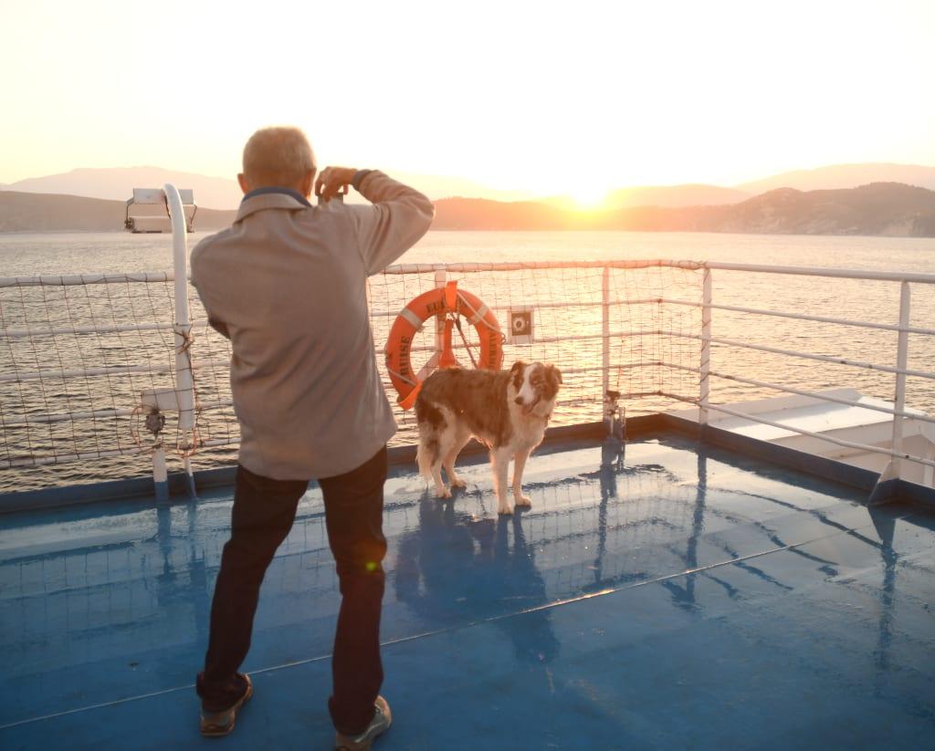 Mann fotografiert Hund auf Schiff