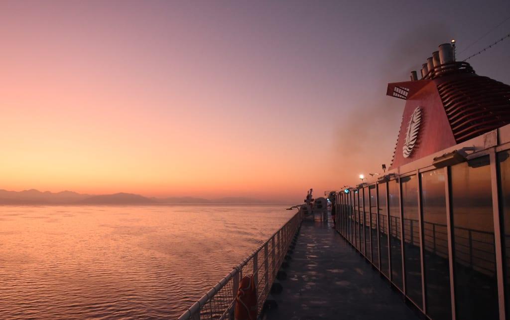Sonnenaufgang über Küstenlandschaft, fotografiert von Deck eines Schiffes