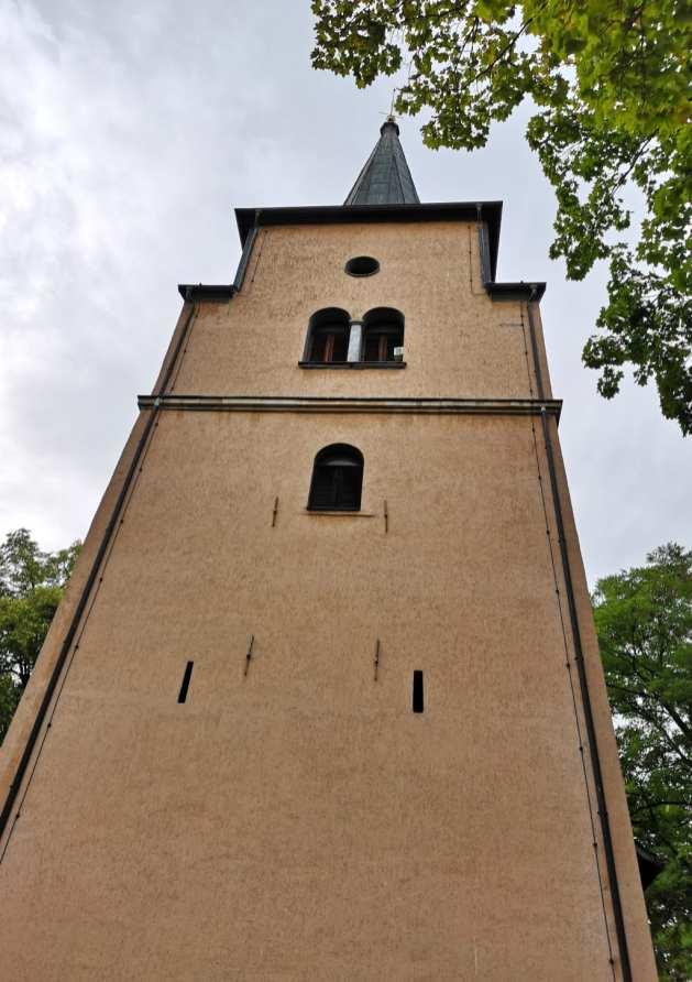 Kirchturm vor grauem Himmel