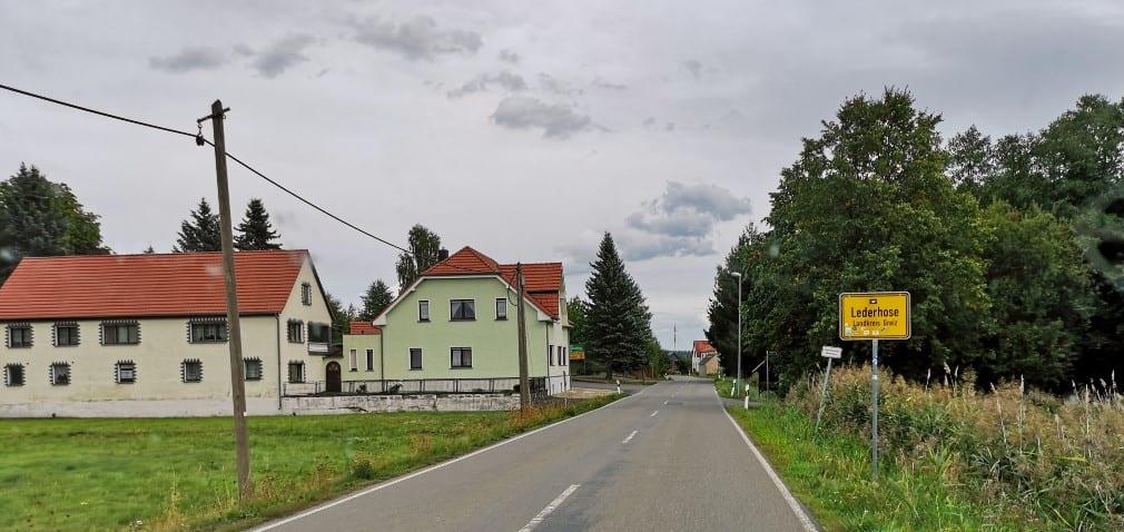 Dorfeingangsschild Lederhose