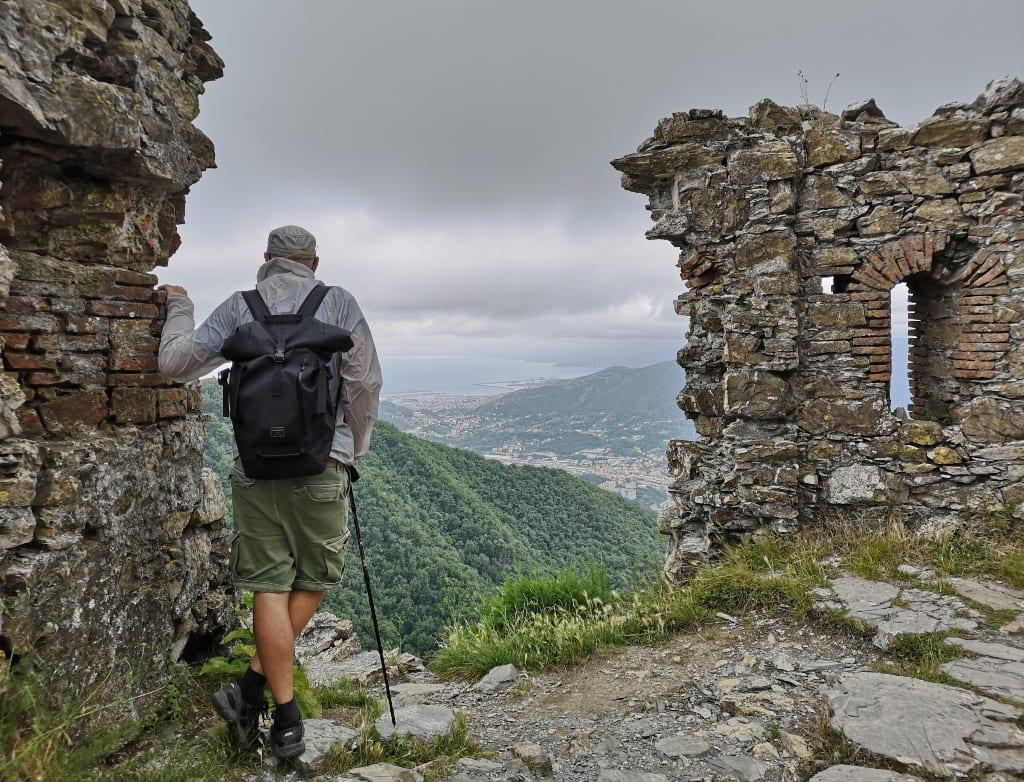 Mann steht in Ruinen und blick über eine Stadt