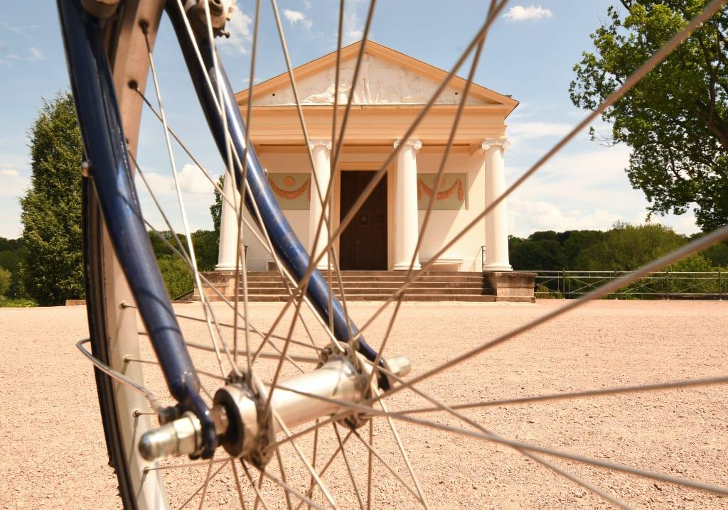 Klassizistisches Gebäude, davor Radspeichen