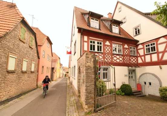 Radlerin radelt durch ein Dorf mit schönem Fachwerk
