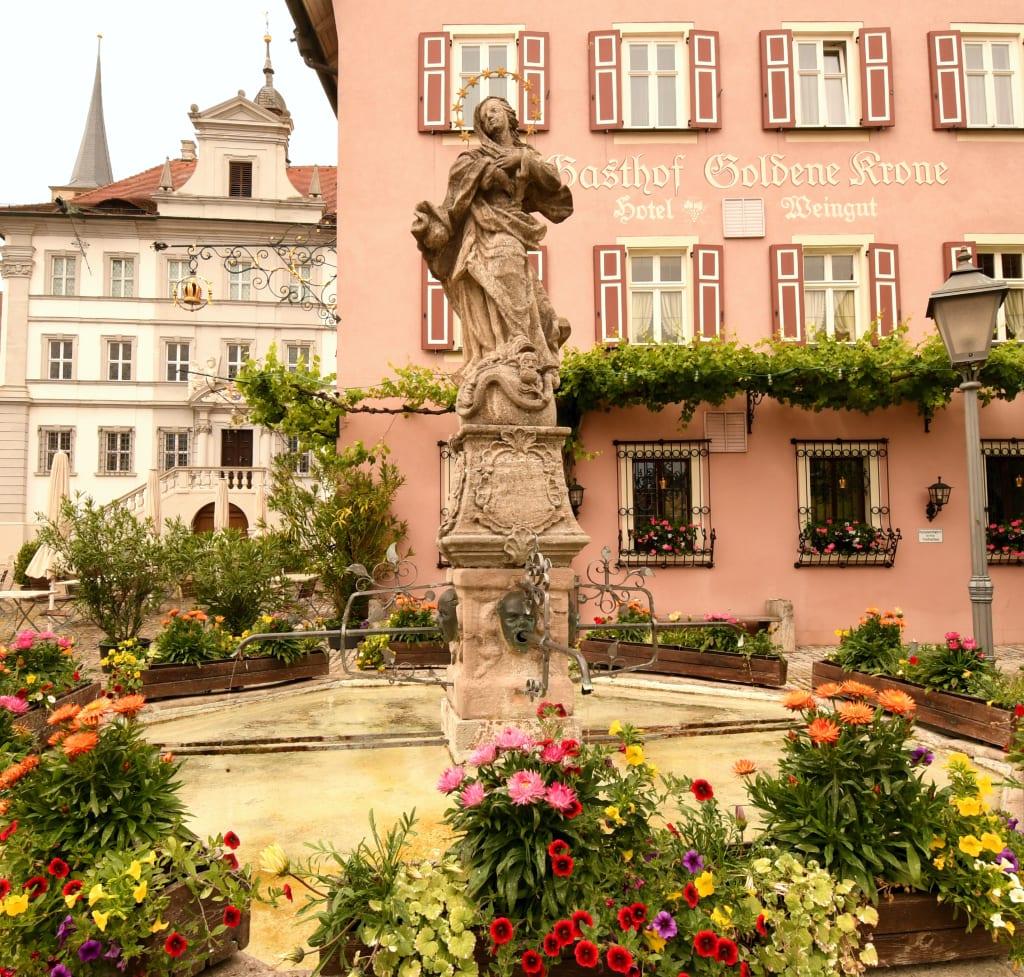 Brunnen mit Blumen, dahinter hübsche Altstadt