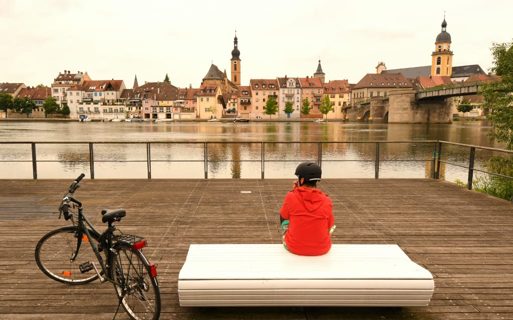 Frau sitzt an einem Fluss