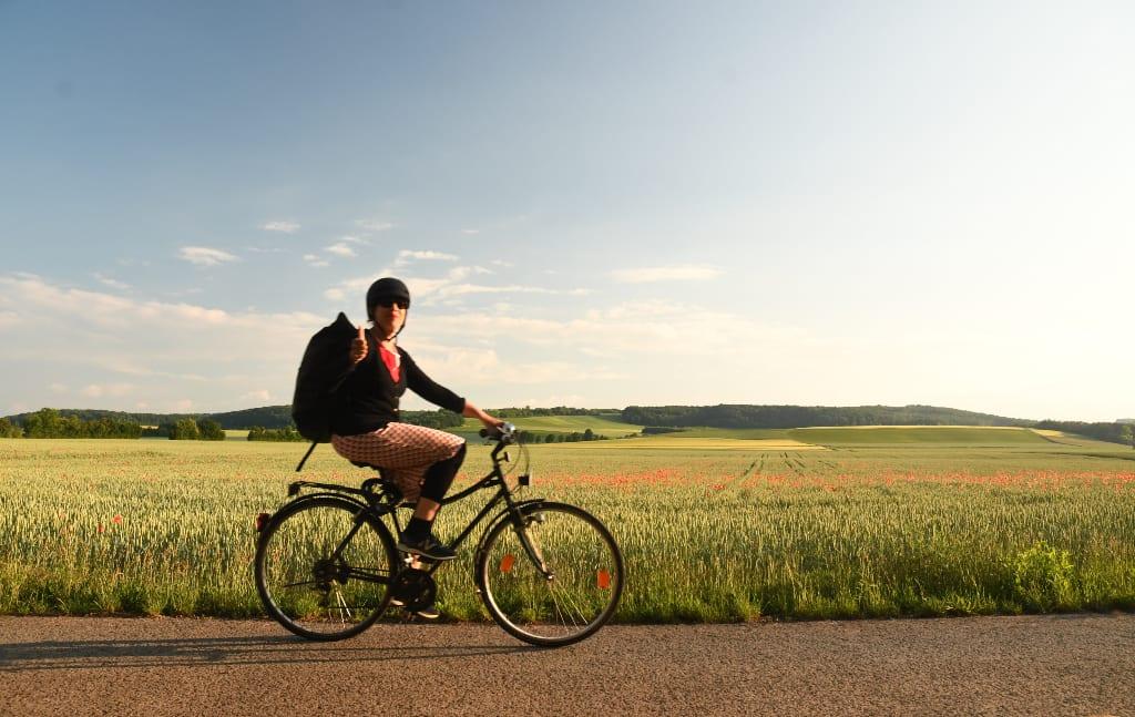 Radfahrerin mit gestrecktem Daumen auf einem Rad