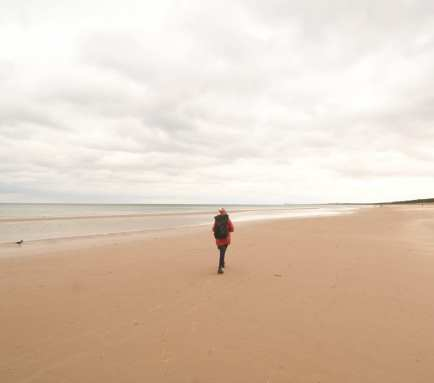 Frau wandert an leerem Winterstrand