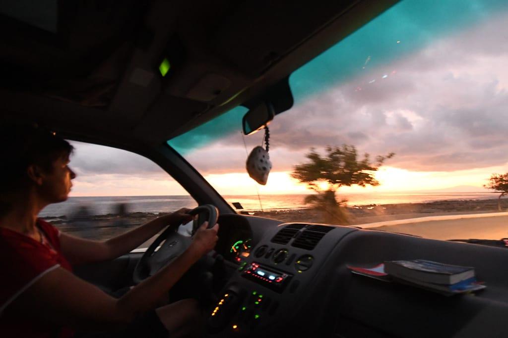 Frau sitzt am Steuer eines Autos im Sonnenuntergang