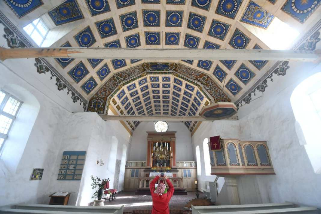 Frau fotografiert Kassettendecke einer Kirche