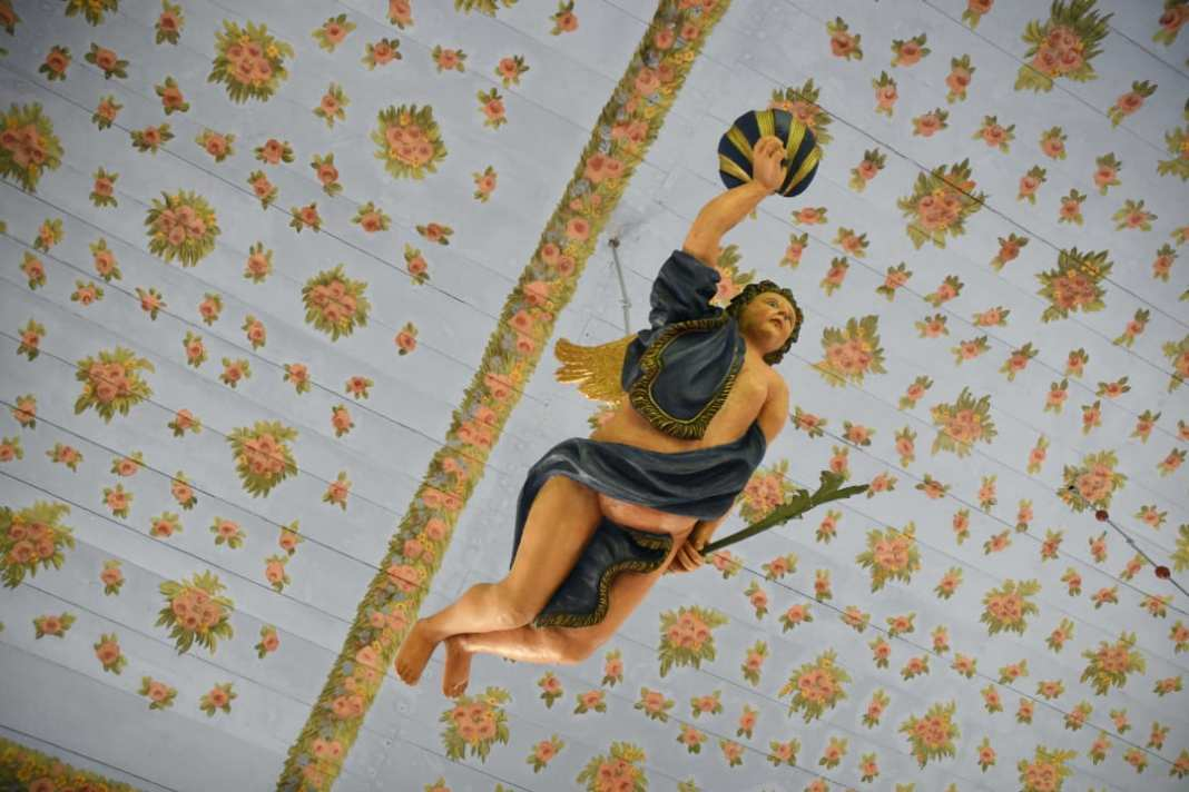Engel hängt unter Blümchendecke