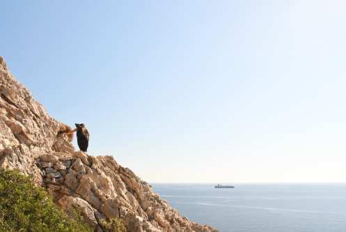 Frau auf Felsen, darunter das Meer