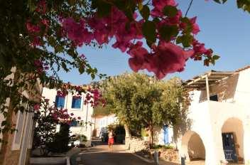 Frau läuft durch griechisches Dorf mit Blumen