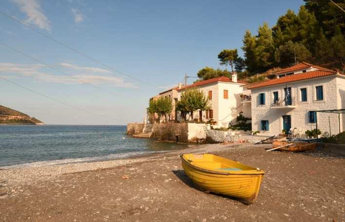Dorf mit weißen Häusern und gelbem Boot am Strand