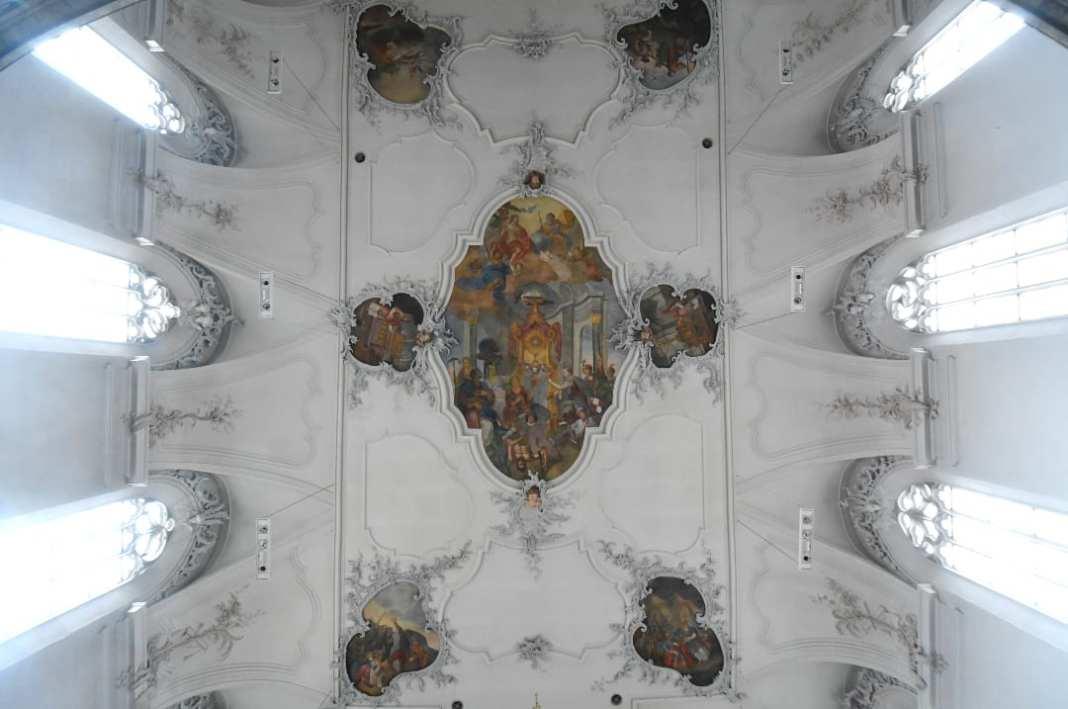 Weiße Stuckdecke einer Kirche mit Fresken