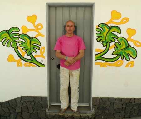 Mann mit rosa T-Shirt steht vor Tür